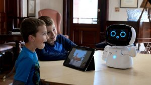 Two young boys happily interacting with Movia Kebbie Robot