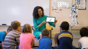 Teacher with young students using a MOVIA robot for instruction